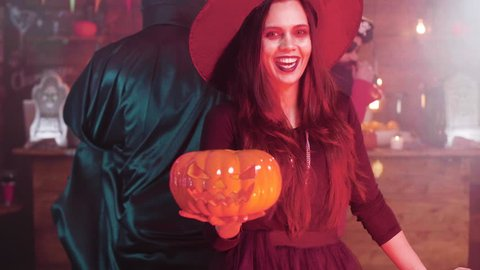 Young woman in a witch costumes make a evil laugh holding a carved pumpkun. Evil witch disguise at a halloween party in a pub.