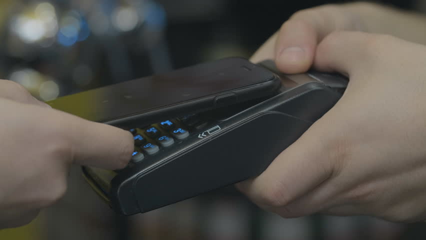 Man paying with NFC technology with smart phone credit card application in clothing store, close-up, point of view, young handsome student male in shopping mall atm banking wallet. | Shutterstock HD Video #1029404087