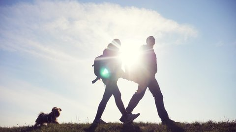 happy family man and woman teamwork walking go hand in hand silhouette of lifestyle tourists on top of mountain sunlight. couple man and girl with backpacks and a dog go at sunset. friendship and