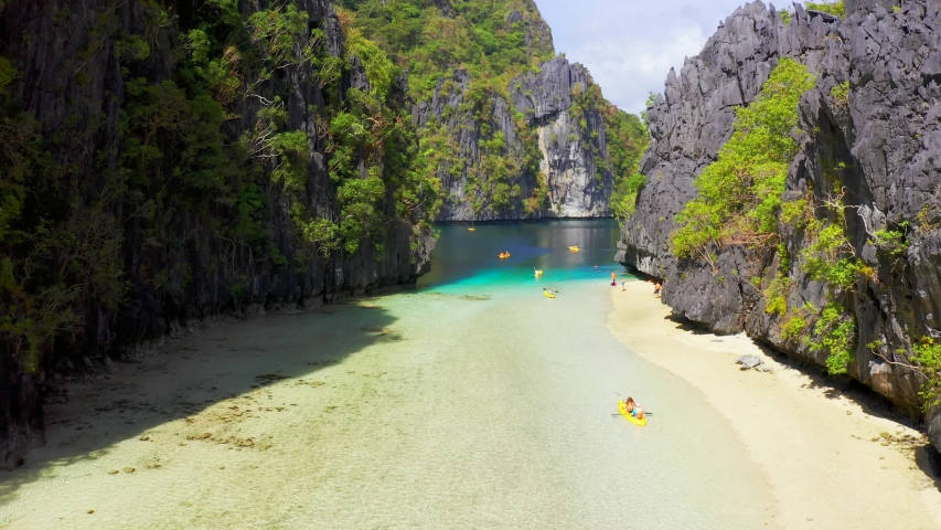 Kayaks in the big lagoon with turquoise clean water, tropical forest, rocks in El Nido island, Palawan, Philippines. Aerial view 4K | Shutterstock HD Video #1029440447
