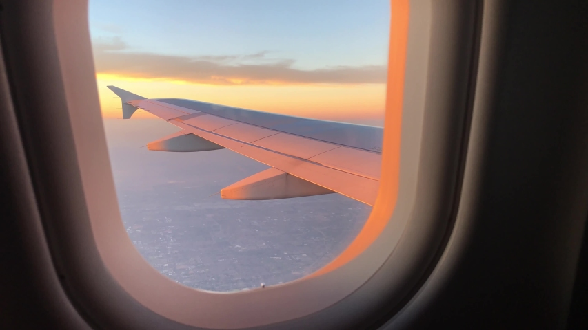Looking out an airplane window at a magnificent and colorful sunset after taking off from the airport. Wing view from window seat. #1029486707
