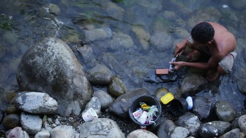 Birds eye view overhead shot of Asian man sharpening knife in river