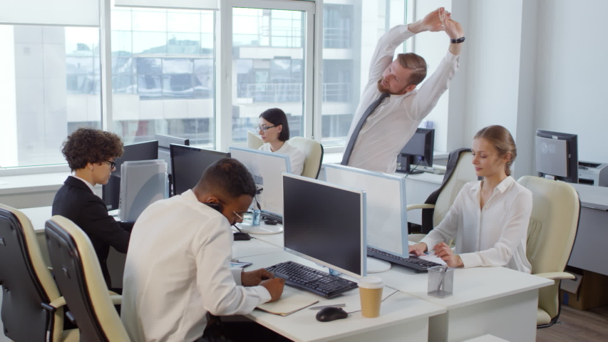 Lockdown of several office workers sitting at desks at computers and working while Caucasian businessman standing up and starting doing physical exercises | Shutterstock HD Video #1029516527