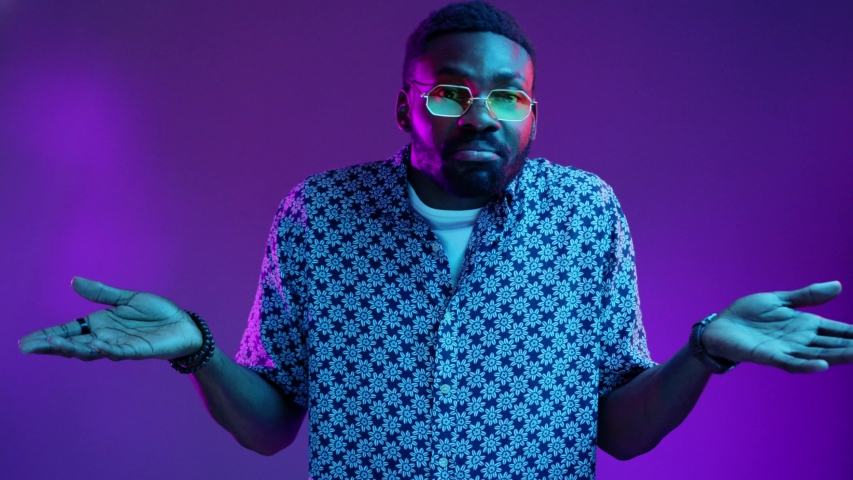 Close up view of handsome Afro American man in stylish tinted sunglasses looks confused and shruggs his shoulders on blank violet background in neon lights. Uncomfortable, surprise, facial expression | Shutterstock HD Video #1029517097