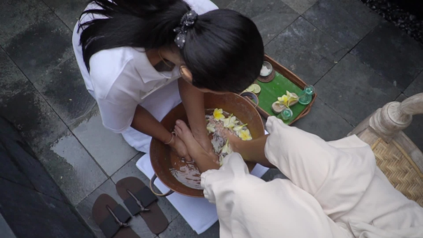 foot bath outside spa, beautician washes girl's feet in tub with flower water #1029579197