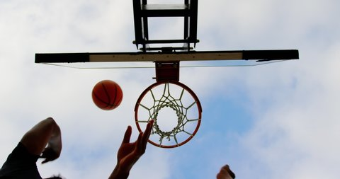 Upward view of multi-ethnic basketball players playing basketball in basketball court. They are making a goal 4k