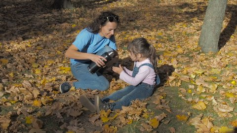 Hot drink in nature. Mother pours tea to the child from a thermos.