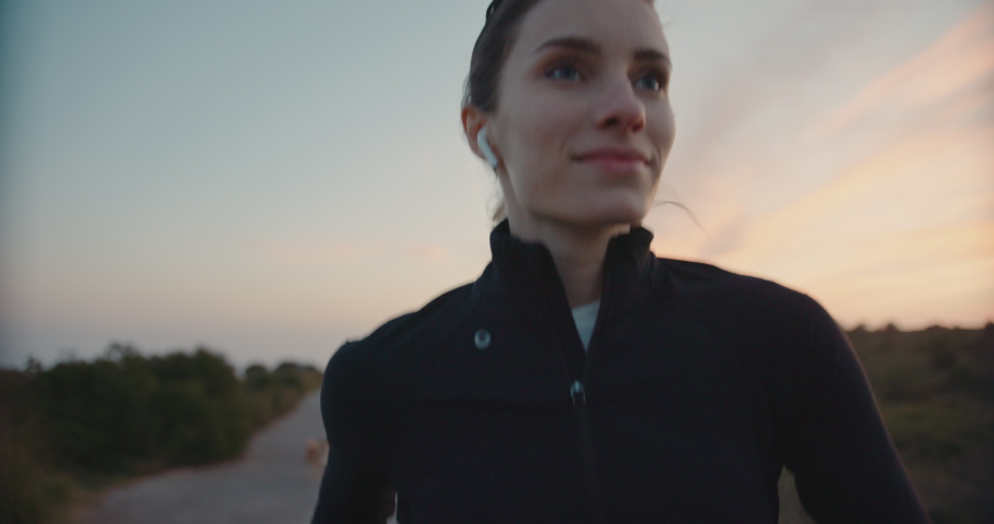 Slow motion shot of young woman running outdoors. Jogging in the countryside during epic sunset. Shot on digital cinema camera | Shutterstock HD Video #1029670727