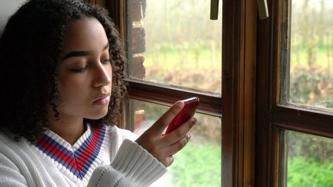 Sad beautiful mixed race African American girl teenager young woman wearing a white jumper, sitting by a window using her mobile cell phone or smartphone for social media, communications or texting