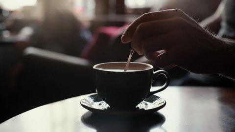 Close up man hand stirring coffee with milk using a spoon. Against the backdrop of cafe and vanity everyday life. In the background a blurred silhouette of a girl