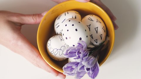 woman lays out a yellow cup on a white background with easter eggs. easter eggs in a yellow cup. white eggs with black pattern. beautiful filet flower on Easter eggs.