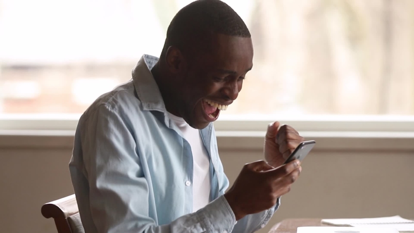 Excited black man winner holding using smartphone feeling overjoyed with mobile online bet bid gambling game win, happy african guy euphoric looking at cell phone celebrate good news victory success | Shutterstock HD Video #1029713897