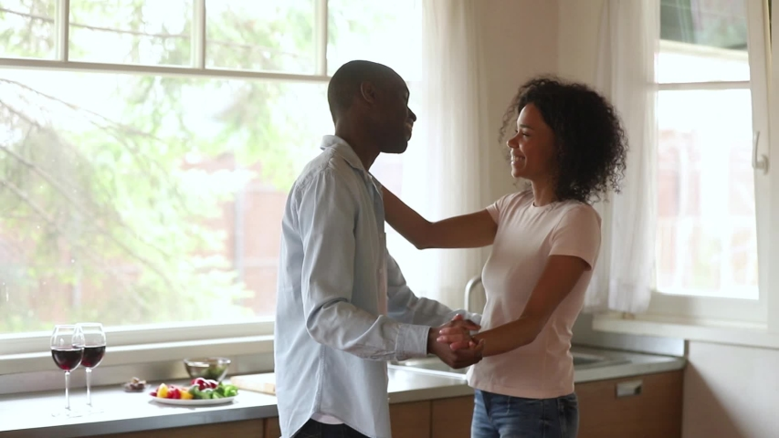 Happy romantic young african american couple in love dancing bonding in kitchen celebrating anniversary cooking together, affectionate black man and woman holding hands enjoy slow dance at home | Shutterstock HD Video #1029714047