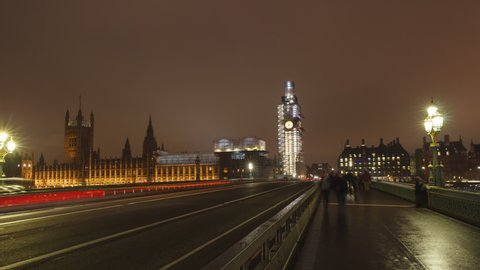 Big Ben time-lapse on the Westminster Bridge in London at Night , hyper lapse slow movement to the Big Ben. Long shutter speed with long light trails. Big Ben is under refurbishment.