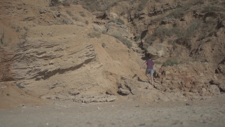 Man walking bare feet on sand with rocks, climbing and walking outdoor slow motion. Low angle shot. Real life urban escape concept | Shutterstock HD Video #1029761417