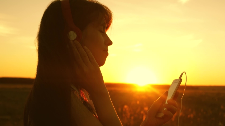 happy girl listening to music and dancing in the rays of beautiful sunset. young girl in headphones and with a smartphone touches finger to the sensor of tablet selects songs online. Slow motion. #1029803117