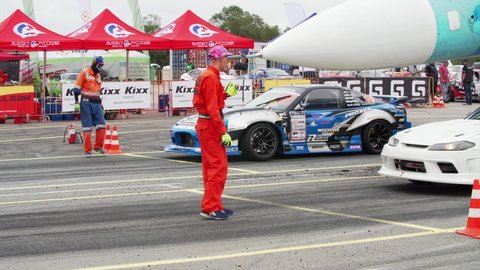 VLADIVOSTOK, RUSSIA - SEPTEMBER 15, 2018: Cars come to the start line. Nose of russian jet fighter aircraft MIG-29 is above them. Asia Pacific D1 Primring GP, International drifting race