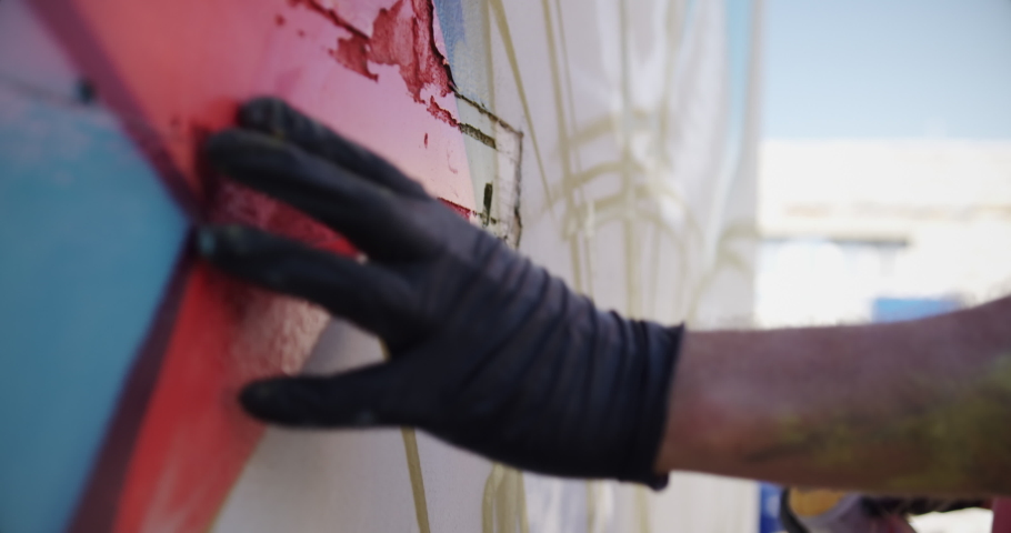 Close-up of Caucasian graffiti artist touching the painted wall. He is shaking aerosol can 4k