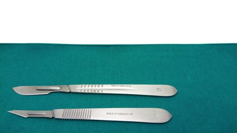 Bangkok / thailand - april 21, 2019 : slide shot of basic surgical  instrument, scalpel handle number 4 with blade number 22 and scalpel handle  number 3 with blade number 11 on green drape fabric