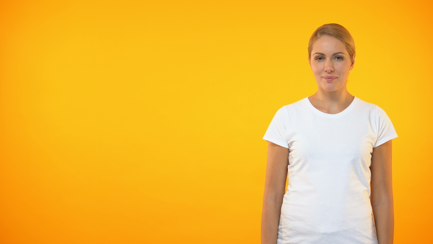 Young smiling woman presenting template on orange background, announcement   Shutterstock HD Video #1029942797