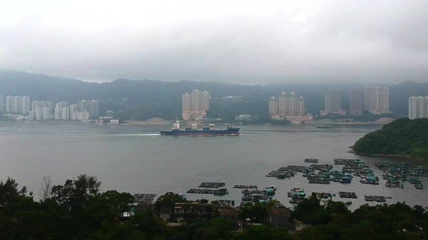 A cargo ship crosses Tung Wan Bay near the Ma Wan Island, Hong Kong. A panoramic view from a quadcopter | Shutterstock HD Video #1029959627