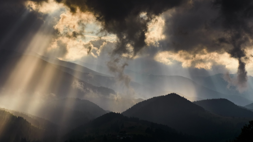Timelapse of sun rays emerging though the dark storm clouds in the mountains