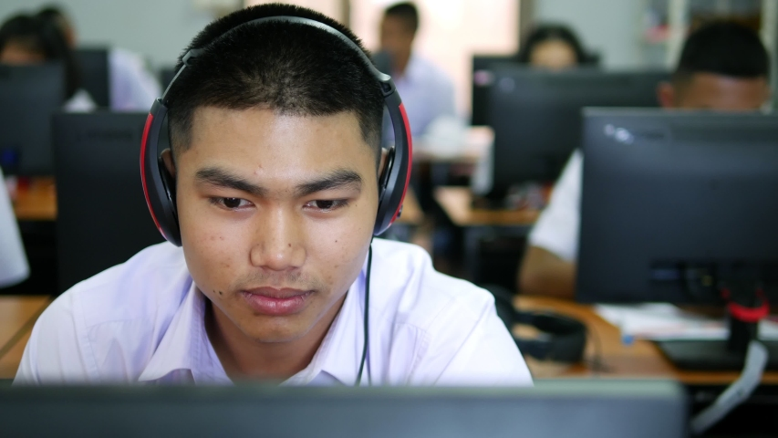 Asian high school male students wearing headphones are laughing and enjoying social media in computer class.   Shutterstock HD Video #1029995417