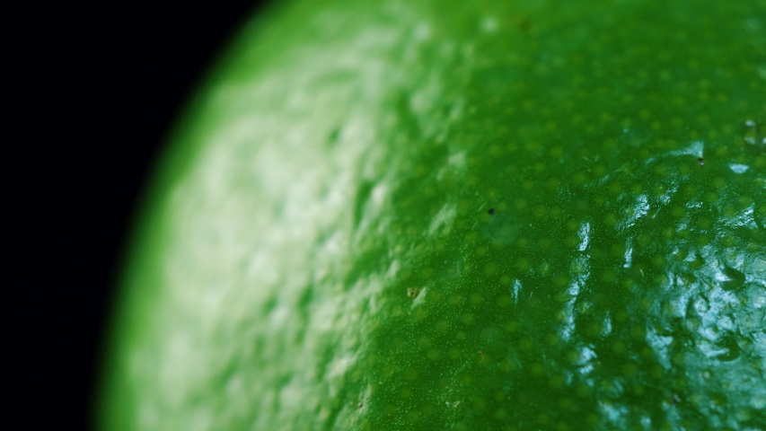 Macro shot of fresh green lime rotating on dark surface. 4K close up footage.