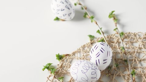 Easter eggs on a white background with flowers. Easter decor. white eggs with black pattern. beautiful easter decoring. female hand removes easter egg.