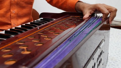 Close up shot of a man playing Indian traditional musical instrument harmonium.