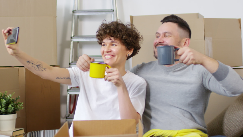 Waist-up shot of happy Caucasian couple in their mid-thirties sitting in their new flat surrounded by moving boxes, taking selfies with smartphone, smiling and toasting each other with tea mugs   Shutterstock HD Video #1030095377