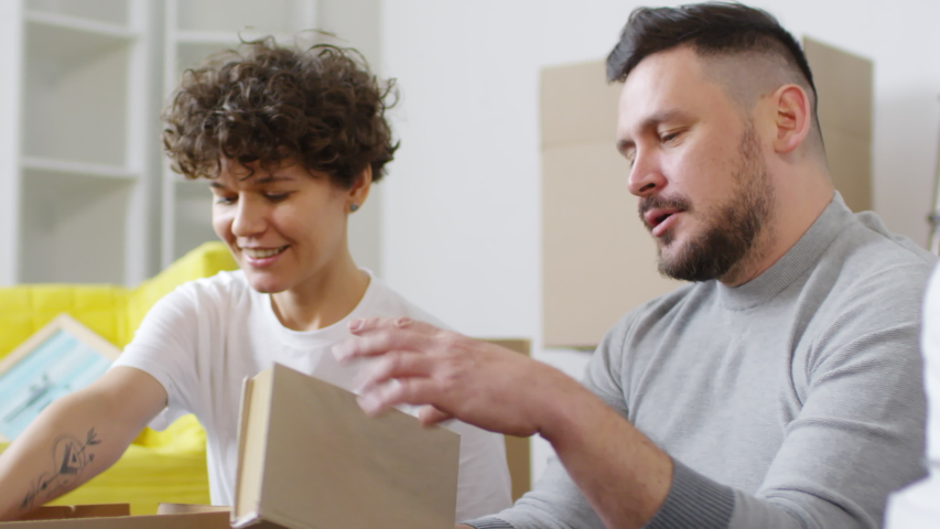 Panning tilting shot of middle-aged Caucasian couple unpacking in their new home, sitting on floor among cardboard boxes and furniture, taking out and admiring together framed pictures and books   Shutterstock HD Video #1030095707