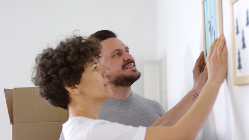 Panning chest-up side shot of middle-aged Caucasian husband carefully hammering small nail into wall of new house, then watching and smiling as his wife puts up framed picture next to another one   Shutterstock HD Video #1030118537