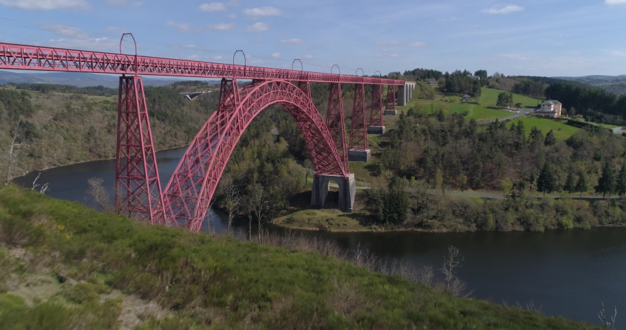 Garabit viaduct appearing behind trees | Shutterstock HD Video #1030120547