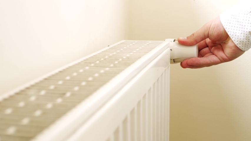 Person's Hand Adjusting Temperature On Thermostat To Control Heat In Central Home Heating System. Radiator near white wall. House in winter concept | Shutterstock HD Video #1030127237