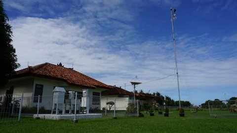 Timelapse a group of white cirrus and altocumulus clouds in the bright blue sky, Time lapse shot of white cirrus and altocumulus passing overhead, above a house building and green grass in Indonesia