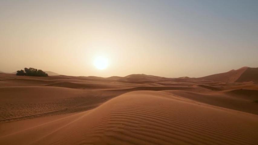 Golder sand close up Sahara desert. Sunset. Sand dunes and blue sky. Beautiful desert landscape. Sahara desert. Sand dunes Arabian desert. Sand dunes wave pattern. Nature background, morocco