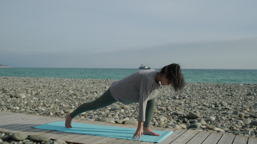 Young active girl doing Warrior I pose on yoga mat outdoor on pebble beach shore, sports activities. Connecting world energy to her body.