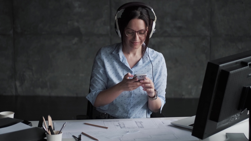 Young woman listening to music with headphones in the office. portrait of a girl resting during work. | Shutterstock HD Video #1030199927