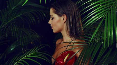 Beautiful girl with tanned skin holds  red exotic flower in her hands being among the tropical plants. Natural makeup and wet hair in girl amazon. Natural cosmetics, spa procedures.