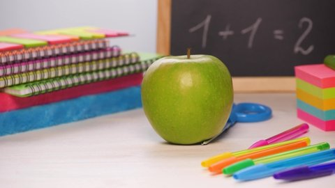 Shot of a school desk with different colorful supplies, and chalkboard. Green apple rolling in. Back to school concept. Sliding focus. 4k.
