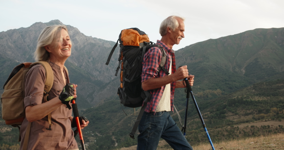 Positive mature caucasian couple trekking in mountains with backpacks, enjoying their adventure 4k #1030289057