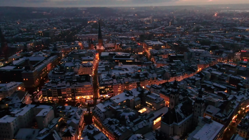 Aerial shot of Bonn city at night in winter. Snow covered city at night. city lights at night, German-city covered in snow, night drone shot of city at-night covered in snow.