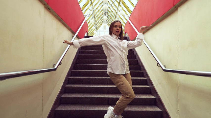 A girl in a white shirt dancing Vogue. Under the big bridge in Moscow on the stairs she dances alone. | Shutterstock HD Video #1030297037