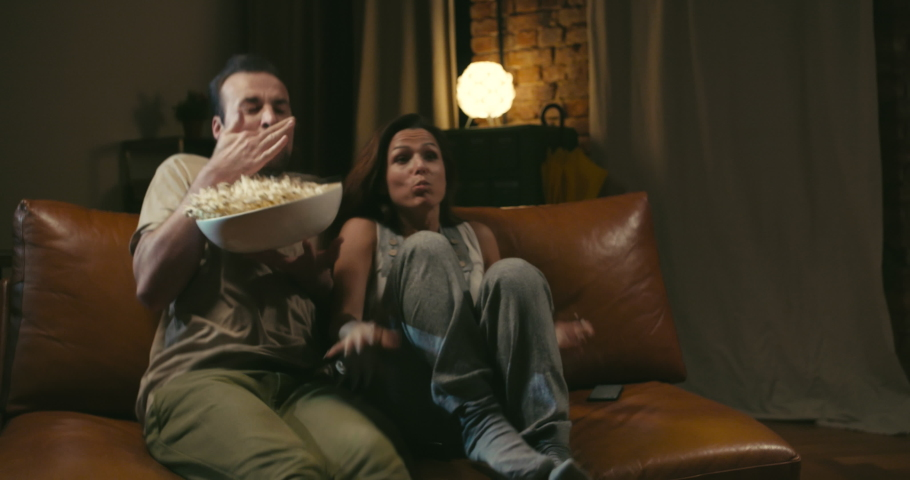 Scared caucasian couple watches movie on couch and eats popcorn at home. They spill popcorn because of unexpected scene | Shutterstock HD Video #1030305527