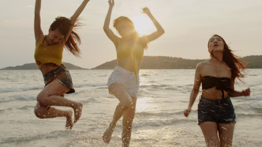 Group of Asian young women running on beach, friends happy relax having fun playing on beach near sea when sunset in evening. Lifestyle friends travel holiday vacation summer concept. Slow motion shot