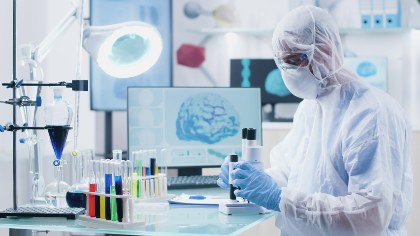 Chemist scientist looking into microscope in modern high end laboratory with 3D scans of brain and DNA on the displays | Shutterstock HD Video #1030333187