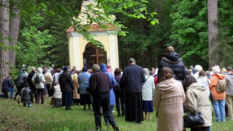 VILNIUS, LITHUANIA - JUNE 02, 2017: Religious people kneel and pray in front of wooden cross near chapel. Catholic Pentecost Sunday. Static shot. 4K UHD
