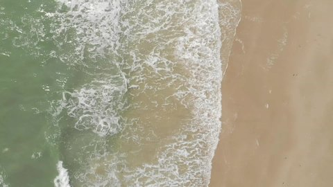 Aerial view waves break on white sand beach. Sea waves on the beautiful beach aerial view drone slow motion