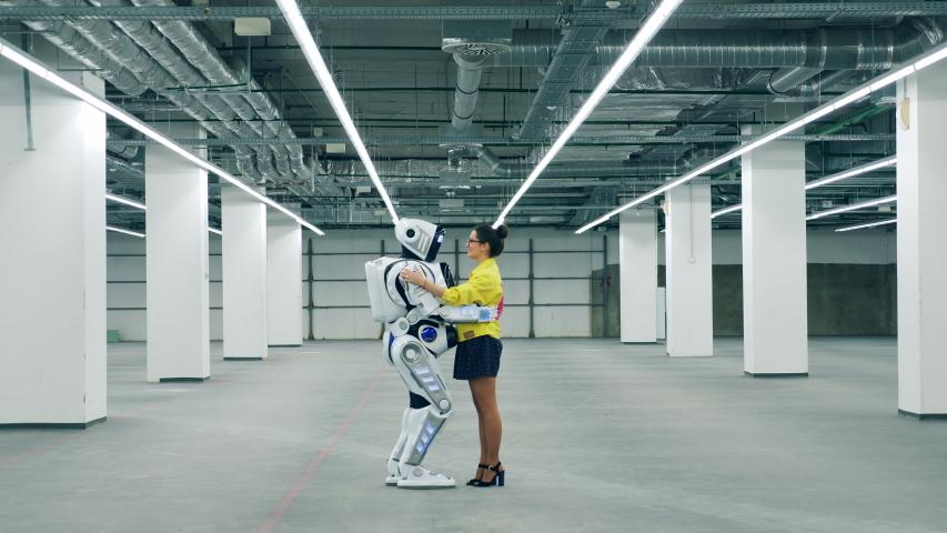 A woman hugs meets her friend robot, hugging it. | Shutterstock HD Video #1030374437